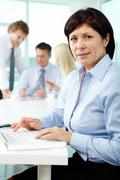mature businesswoman at workplace looking at camera in working environment - stock photo