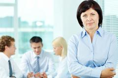 Mature businesswoman looking at camera in working environment Stock Photos