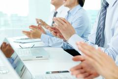 Business people sitting in a row applauding to their successful colleague Stock Photos
