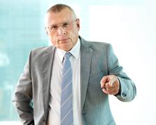 Portrait of serious mature businessman pointing and looking at camera Stock Photos