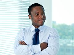portrait of african businessman looking aside in office - stock photo