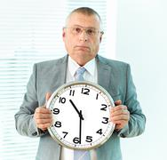 portrait of elderly businessman with clock looking at camera - stock photo
