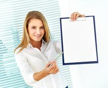 portrait of young businesswoman pointing at clipboard and looking at camera - stock photo