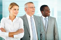 portrait of three successful business partners looking forwards - stock photo