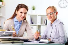 portrait of happy young businesswomen looking at camera in office - stock photo