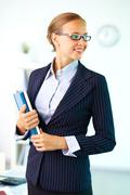 portrait of elegant businesswoman with handbooks looking aside - stock photo