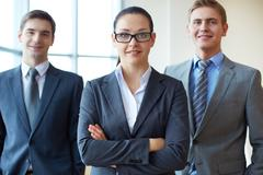 Portrait of a smiling business woman looking at camera with two employees behind Stock Photos