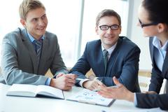 image of two employees looking at businesswoman explaining her idea at meeting - stock photo