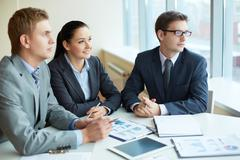 Image of three business people looking in the window at meeting Stock Photos