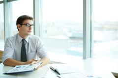 Image of smart businessman with document looking in the office window Stock Photos