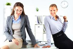Portrait of two young elegant businesswomen looking at camera in office Stock Photos