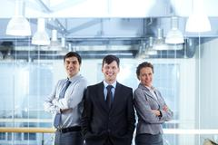 Successful businesspeople looking at camera and smiling Stock Photos