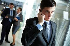 Businessman speaking on the phone, his colleagues discussing business matters in Stock Photos