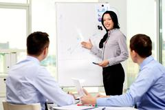 smiling business lady carrying out presentation of a business plan - stock photo