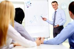 Smiling businessman drawing a graph for his colleagues on the whiteboard Stock Photos