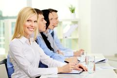 pretty business lady looking at camera while her colleagues listening to someone - stock photo