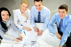 the above view of a business team looking at camera with confident smile - stock photo