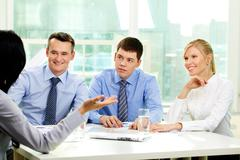 Positive business people listening attentively to their leader Stock Photos