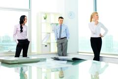 three pensive business people gathered in office - stock photo