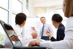 Smiling businessman explaining business ideas to his partners Stock Photos