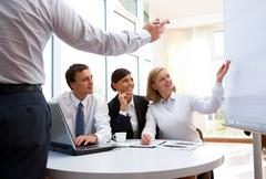 businesspeople sharing ideas concerning new business project - stock photo