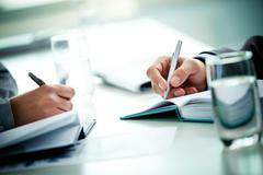 Image of male and female hands with pens over open notebooks at seminar Stock Photos