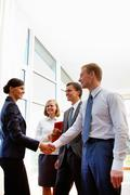 Image of business partners handshaking after signing new contract Stock Photos