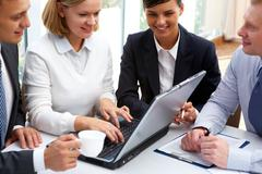 Smiling businesswoman showing her strategy to the partners Stock Photos