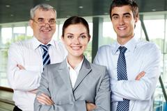 Three smiling business people looking confidently at camera Stock Photos