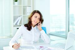 young woman discussing business matters on the phone and taking notes - stock photo