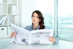 young business woman holding a newspaper and looking at camera - stock photo