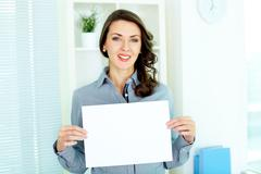 Business woman holding a sheet of paper and looking at camera Stock Photos