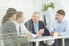 Four people discussing business matters Stock Photos