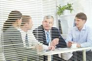 Stock Photo of four people discussing business matters