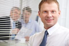 Businessman looking at camera with a smile, his colleagues being in the backgrou Stock Photos