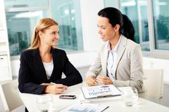 portrait of two young businesswomen planning work and looking at each other - stock photo