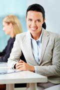 portrait of a young woman at her workplace looking at camera and smiling - stock photo