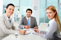 Three business people looking at camera in office Stock Photos