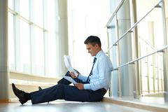 portrait of nervous businessman sitting on the floor with papers - stock photo