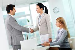 Portrait of successful associates handshaking after striking deal Stock Photos