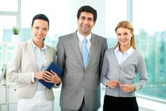 Three business people in formalwear looking at camera in office Stock Photos