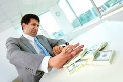 Image of disgusted male employee moving dollar bills away and refusing to take b Stock Photos
