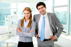 two business partners in formalwear looking at camera in office - stock photo