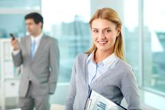 smiling businesswoman looking at camera with busy man on background - stock photo
