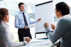 confident businessman and his partners discussing something on a whiteboard - stock photo