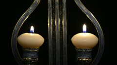 Two white candles in a candlestick form of lyre Stock Footage