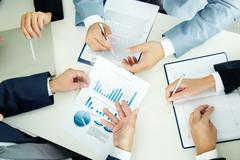 image of busiess group discussing business documents at meeting - stock photo
