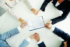Image of businesspeople hands in hold with document in the center Stock Photos