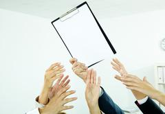 Image of several human hands trying to get paper from male hand Stock Photos