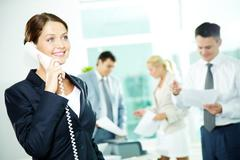 a beautiful businesswoman calling by the phone in working environment - stock photo